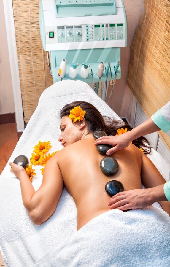 Mulher que obtem uma massagem de pedra quente no salão de beleza dos termas fotografia de stock royalty free