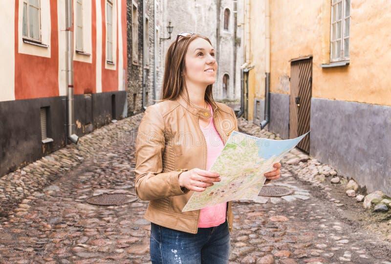 Mulher que olha acima e que guarda o mapa Viajante de sorriso que sightseeing imagem de stock royalty free