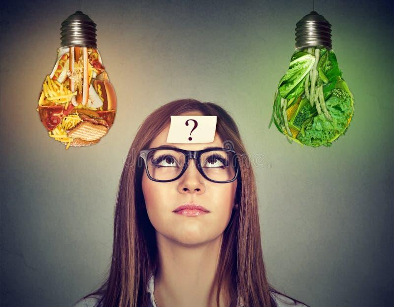 Mulher que olha a ampola da comida lixo e dos vegetais verdes imagem de stock royalty free