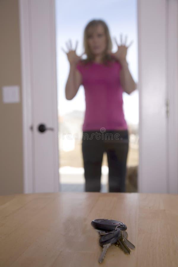 Mulher que olha através da porta em chaves fotografia de stock