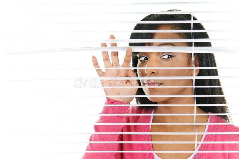Mulher que olha através das cortinas venetian fotos de stock royalty free