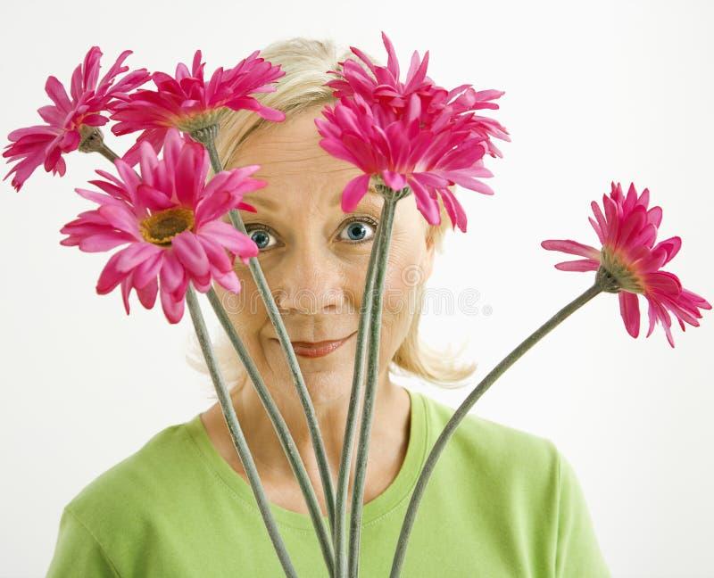 Mulher que olha através das flores. foto de stock royalty free
