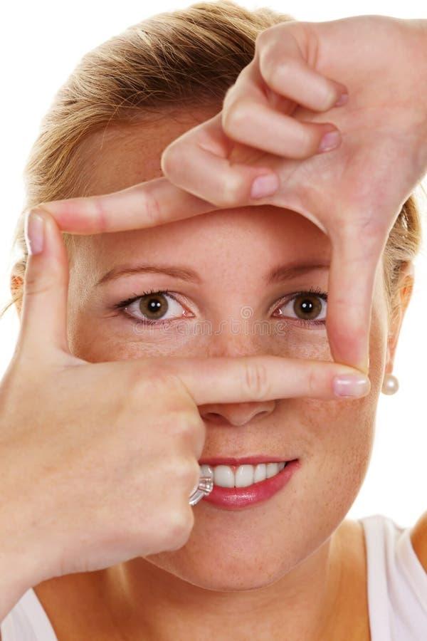 Mulher que olha através de um frame foto de stock