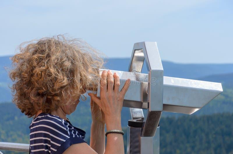 Mulher que olha através de um telescópio binocular imagens de stock