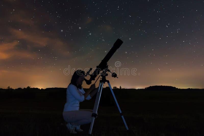 Mulher que olha através de um telescópio que olha as estrelas imagens de stock royalty free