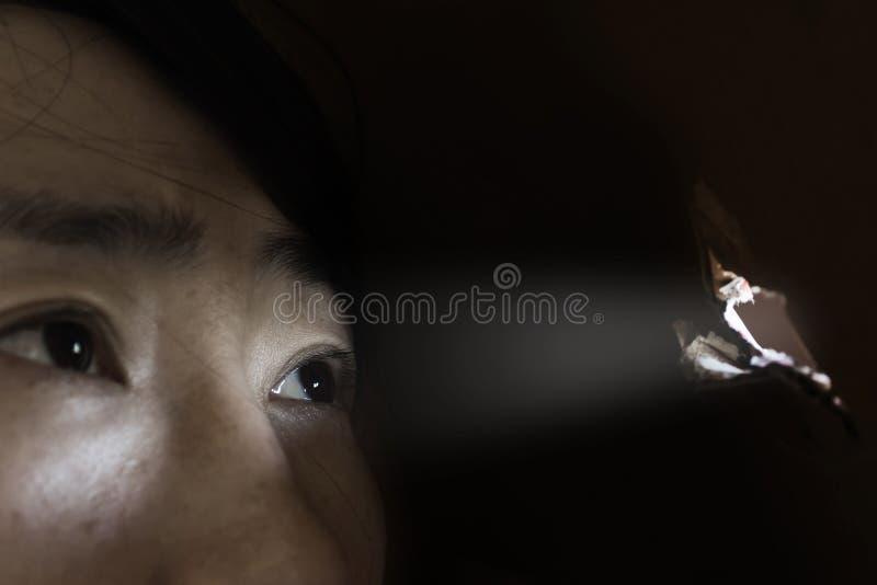 Mulher que olha através do furo com conceito do lightabuse imagens de stock royalty free