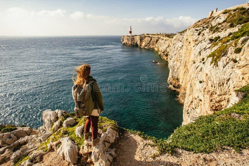 Mulher que olha através do oceano azul profundo ao lado do penhasco fotografia de stock