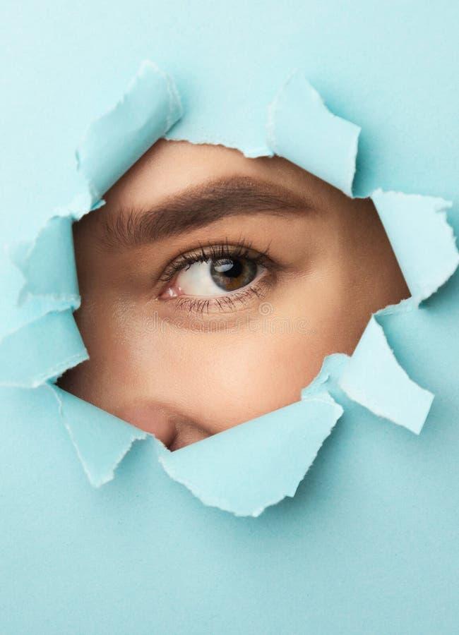 Mulher que olha através do papel azul rasgado, close up imagens de stock royalty free