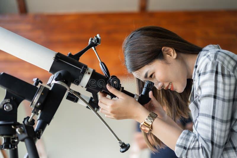 Mulher que olha através do telescópio fotografia de stock royalty free