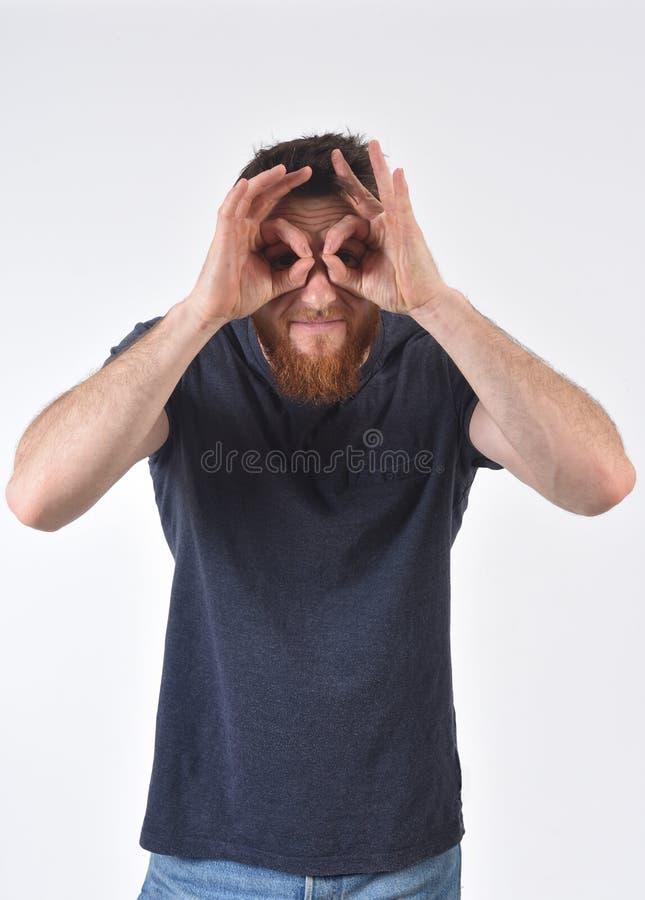 Mulher que olha atrav?s dos dedos como se vestindo vidros no fundo branco foto de stock royalty free
