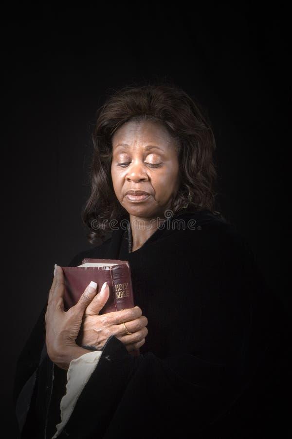 Mulher que olha a Bíblia imagem de stock royalty free