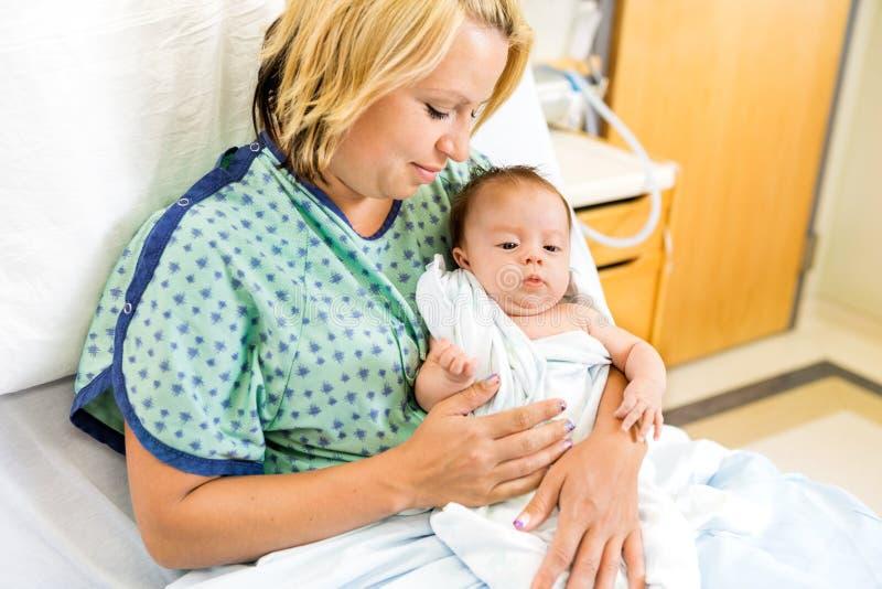 Mulher que olha Babygirl na cama de hospital imagens de stock royalty free