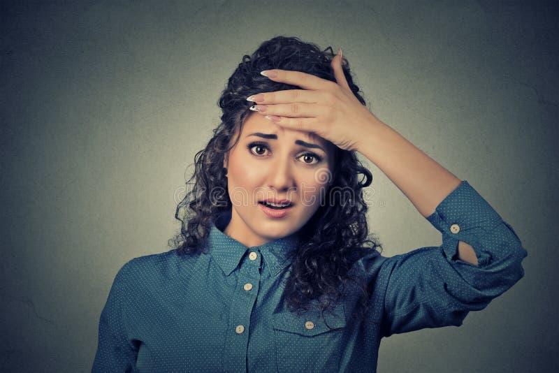 A mulher que olha chocada, surpreendido, mão na cabeça forçada realizou o erro fotos de stock