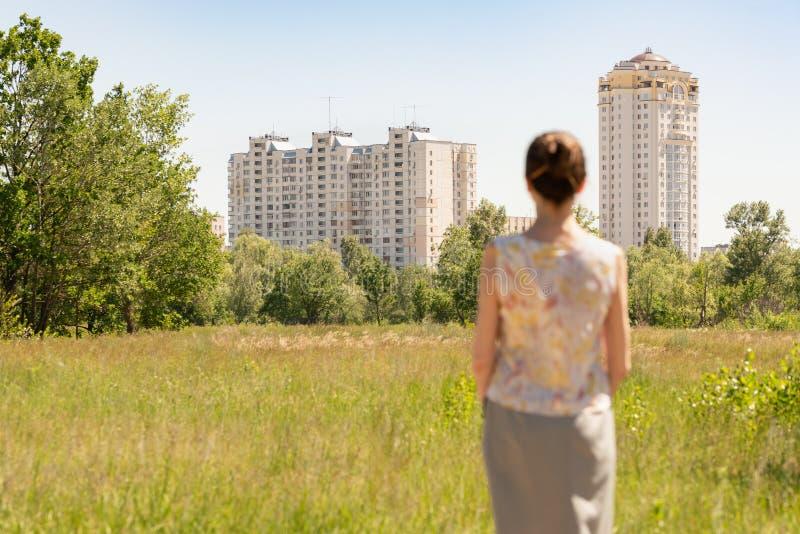 Mulher que olha construções residenciais modernas fotografia de stock