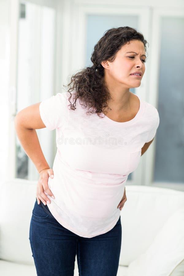 Mulher que olha de sobrancelhas franzidas na dor nas costas foto de stock royalty free