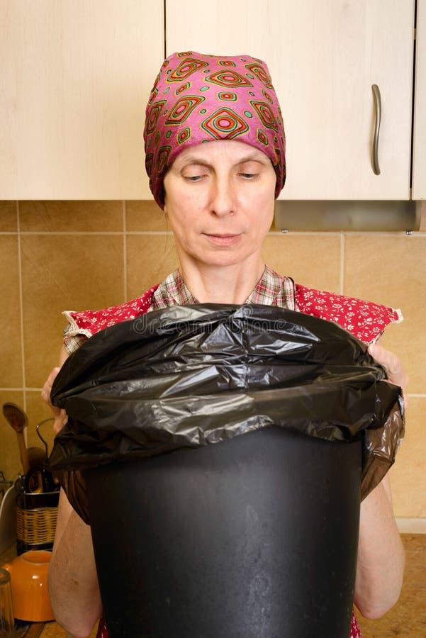 Mulher que olha dentro de um balde do lixo fotografia de stock royalty free