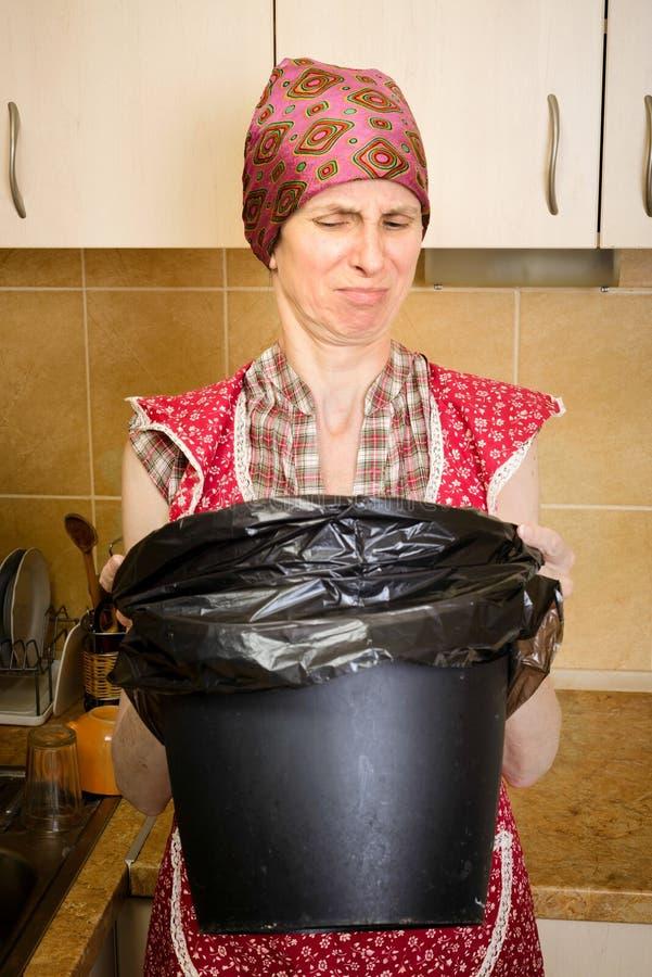Mulher que olha dentro de um balde do lixo imagens de stock