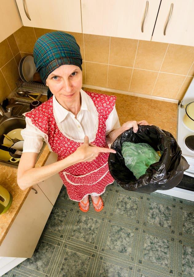 Mulher que olha dentro de um balde do lixo foto de stock