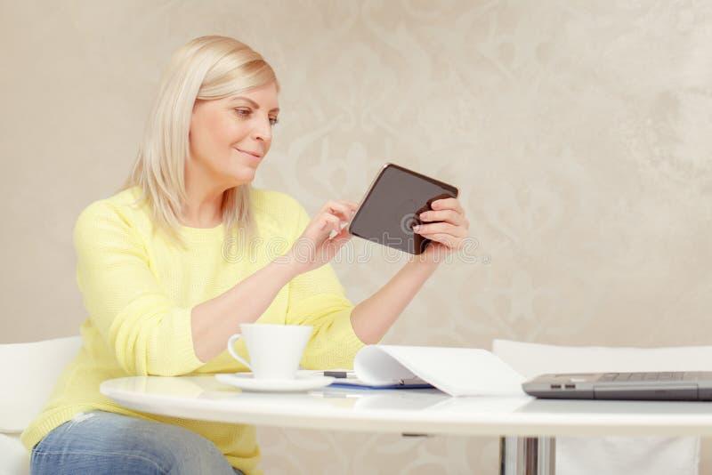 Mulher que olha em seu dispositivo da tabuleta imagem de stock