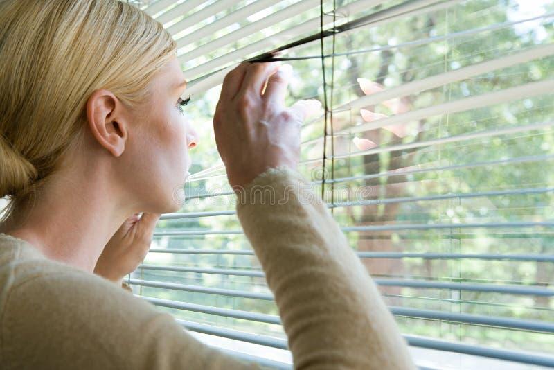 Mulher que olha fora das cortinas imagens de stock royalty free