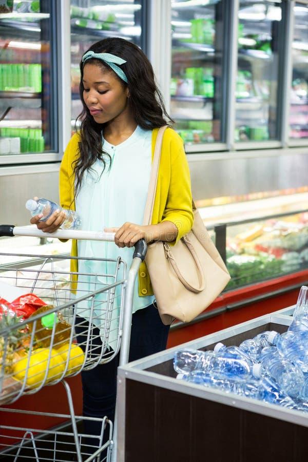 Mulher que olha a garrafa da água na seção do mantimento foto de stock royalty free