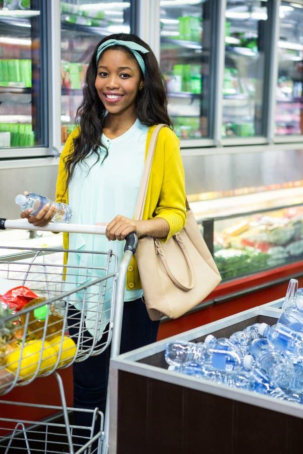 Mulher que olha a garrafa da água na seção do mantimento no supermercado foto de stock