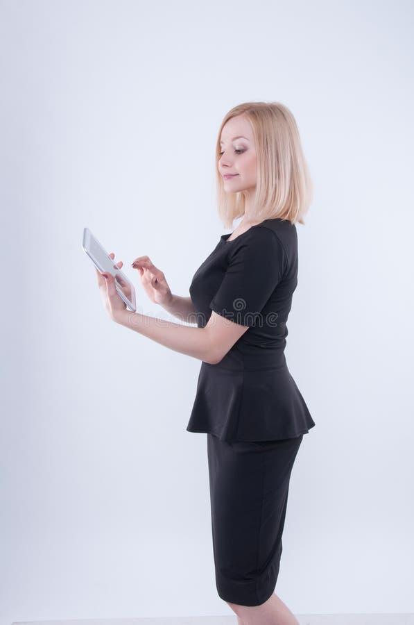 Mulher que olha na tabuleta branca em suas mãos Feche acima da menina bonita loura nova no vestido preto usando a tabuleta fotografia de stock