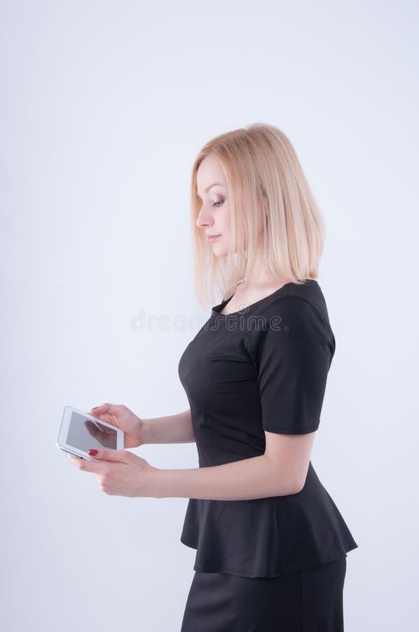 Mulher que olha na tabuleta branca em suas mãos Feche acima da menina bonita loura nova no vestido preto usando a tabuleta fotos de stock