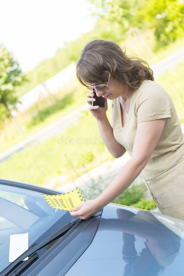Mulher que olha no bilhete de estacionamento imagens de stock