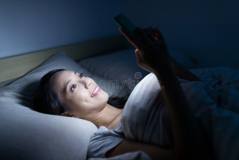 Mulher que olha no telefone celular na noite fotos de stock