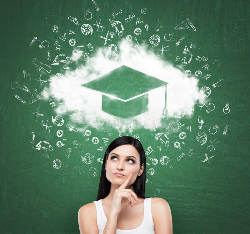 Mulher que olha a nuvem com o chapéu da graduação sobre a cabeça Placa de giz verde como um fundo imagens de stock