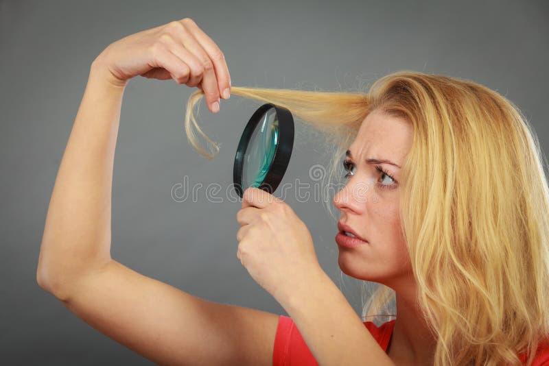 Mulher que olha o cabelo através da lupa imagem de stock