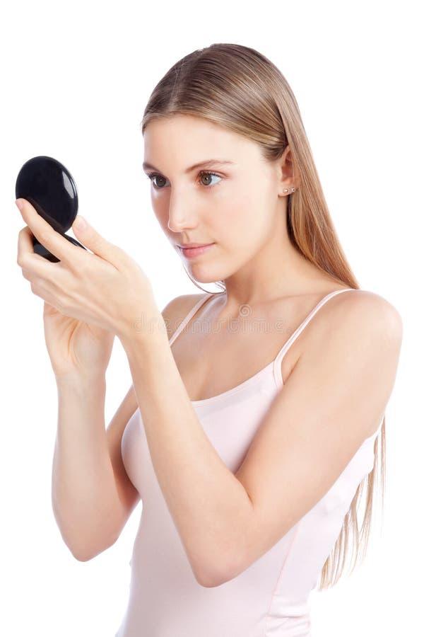 Mulher que olha o espelho compacto fotografia de stock