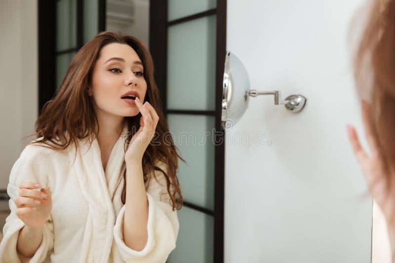 Mulher que olha o espelho e os bordos tocantes no banheiro fotografia de stock royalty free