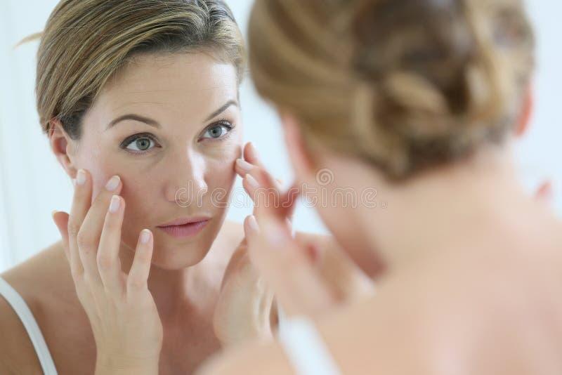 Mulher que olha o espelho que aplica um creme fotos de stock royalty free