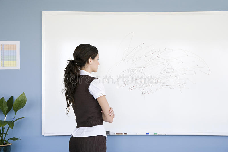 Mulher que olha o garrancho no whiteboard imagem de stock royalty free