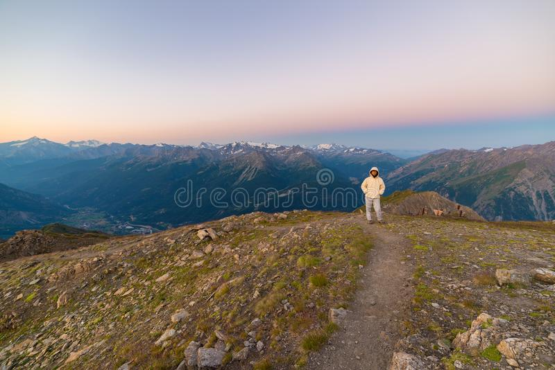 Mulher que olha o nascer do sol impressionante sobre vales, cumes e picos de montanha Opinião de ângulo larga de 3000 m no ` Aost imagem de stock royalty free