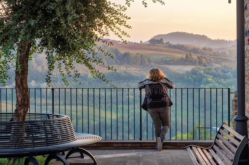 Mulher que olha o panorama crepuscular de Langhe Imagem da cor imagens de stock royalty free
