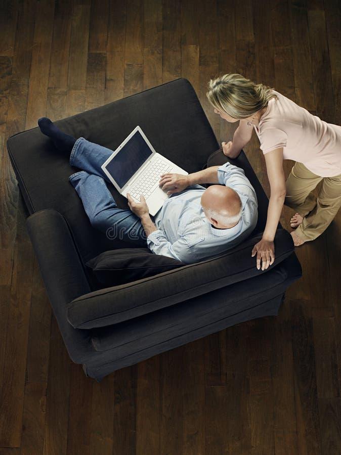 Mulher que olha o portátil calvo do uso do homem foto de stock royalty free