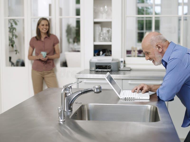 Mulher que olha o portátil calvo do uso do homem na cozinha fotografia de stock