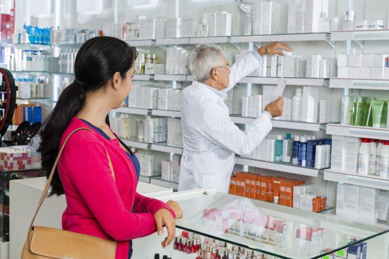 Mulher que olha o químico Searching For Medicine nas prateleiras foto de stock royalty free