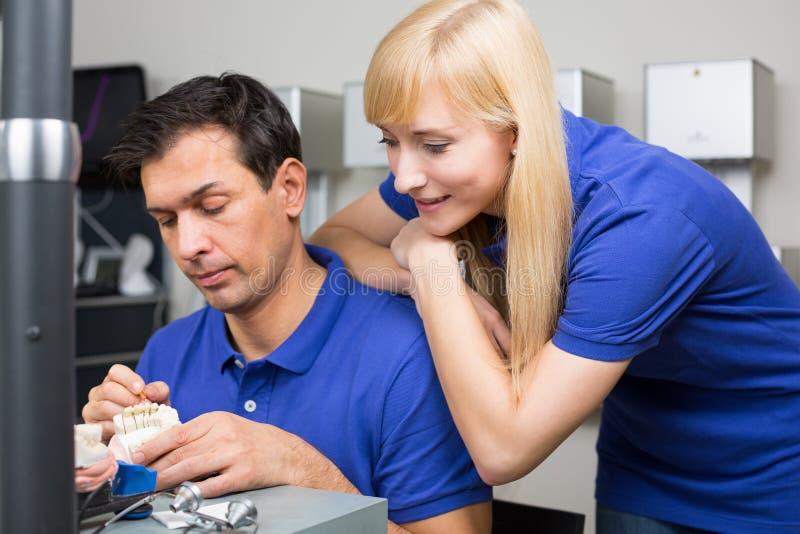 Mulher que olha o técnico dental aplicar a porcelana imagens de stock