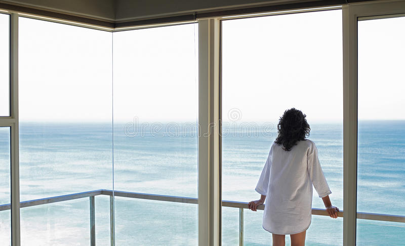 Mulher que olha a opinião do mar do balcão fotos de stock