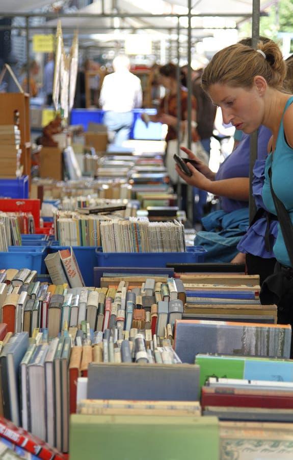 Mulher que olha os livros indicados em uma tenda imagens de stock