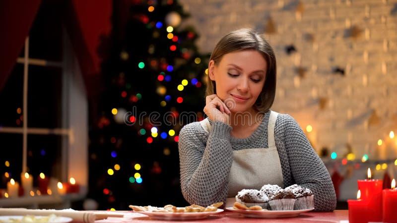 Mulher que olha os queques deliciosos do chocolate, satisfeitos com o cozimento do Natal imagens de stock royalty free