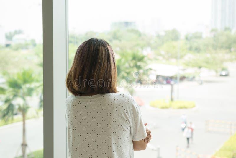 Mulher que olha para fora de sua janela do escritório foto de stock