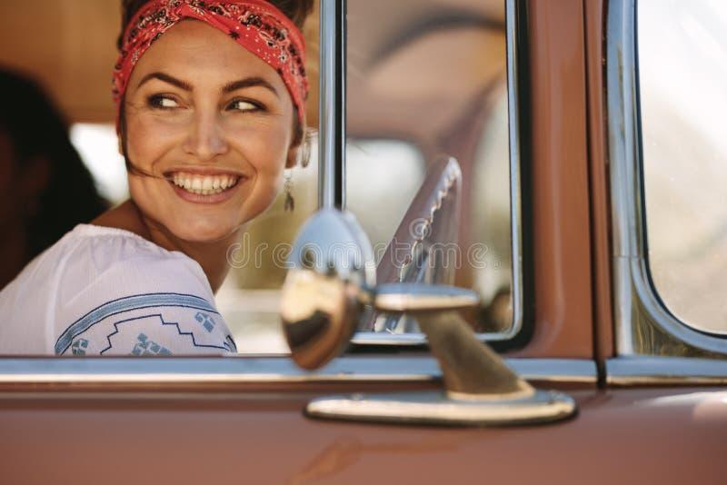 Mulher que olha a parte externa ao conduzir fotografia de stock