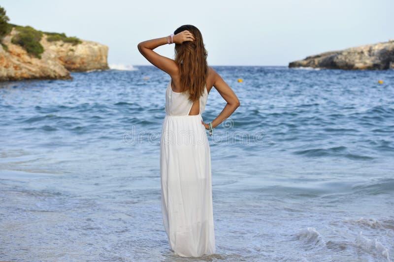 Mulher que olha pensativa na água do mar nas férias de verão que apreciam o vestido branco vestindo relaxado da praia das férias imagens de stock