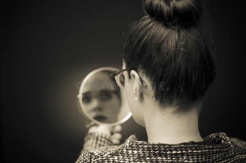 Mulher que olha a reflexão do auto no espelho fotos de stock royalty free
