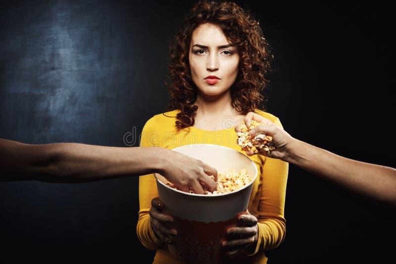 Mulher que olha reta guardando a cubeta da pipoca quando os amigos agarrarem o alimento imagem de stock